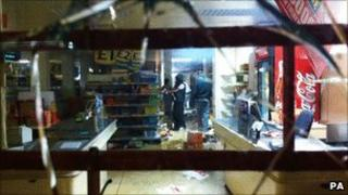 Youths use aerosol cans to set fire to shelves of goods inside a retail store on Tottenham High Road after youths protested against the killing of a man by armed police in an attempted arrest on August 6