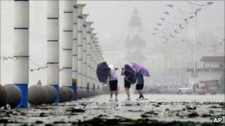 People walk against the wind as tropical storm Muifa hits Yantai, China