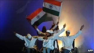 Physically challenged artists in wheelchair hold Indian flags during a performance in Bangalore on 28 May 2010