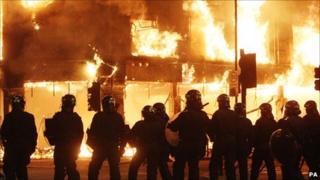 Officers in riot gear near burning shops in Tottenham on Sunday