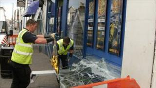 Workers fixing broken window of a Coral bookmakers shop in Barton Street, Gloucester