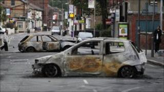 Burned out shells of cars block a road in Toxteth