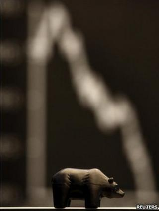 A figure of a bear, symbol for down going bourse trade, is seen in front of the German share price index at Frankfurt's stock exchange