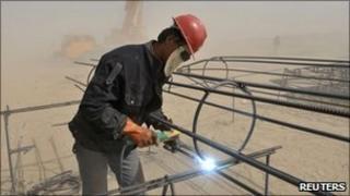 A labourer welds steel bars