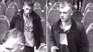 CCTV images of two men standing up on a train