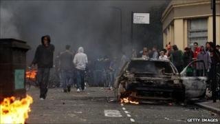 Local residents and rioters look towards the police line from behind a burnt out car in Clarence Road in Hackney on August 8, 2011 in London, England.