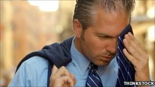 Man wipes away sweat with his tie