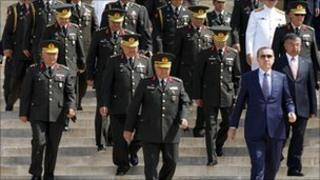 Turkish PM Tayyip Erdogan, in the blue suit, along with senior military officials at a wreath-laying ceremony in Ankara on 8 August 2011