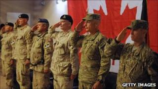 Canadian and American troops salute in Afghanistan