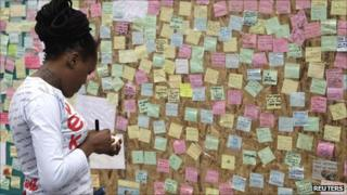 "Woman writing a message for Peckham's ""Wall of Love"""