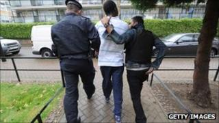 Metropolitan Police officers arrest a man suspected of involvement in the riots after carrying out a raid on a property on the Churchill Gardens estate in Pimlico