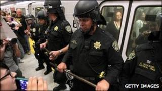 Bart police keep back protesters from a departing train in San Francisco