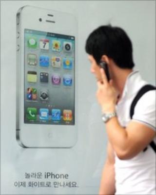 A man walks past an iPhone 4 advert in Seoul