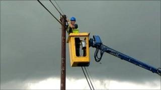 engineer in cherry picker repairing phone line