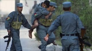 A wounded Afghan policeman is carried away from the site of an attack on offices belonging to the British Council in Kabul August 19, 2011.