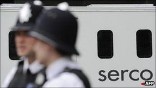 Two police officers with a Serco prison van