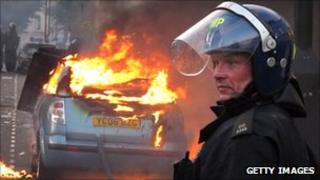 A police officer in riot gear stands near a burning car in Hackney on 8 August