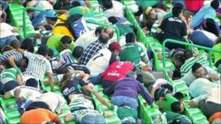 Fans crouch down after hearing gunfire during a football match between Santos Laguna and Monarcas Morelia in Torreon, Mexico, on 20 August