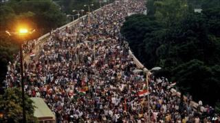 Supporters of Indian activist Anna Hazare march through a flyover in Delhi on Sunday 21 August 2011