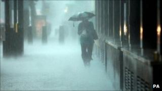 A woman in torrential rain in central London