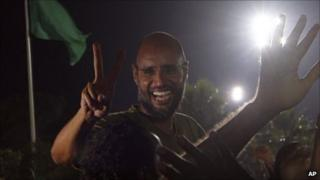 Saif al-Islam gestures to troops loyal to his father in Tripoli in the early hours of Tuesday 23 August
