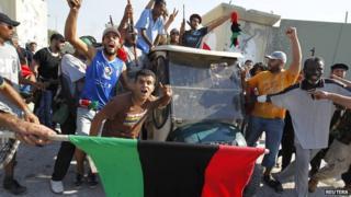 Libyan rebel fighters celebrate entering Colonel Gaddafi's compound in Tripoli.