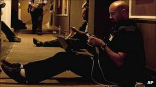 Journalists sit on the floor of a corridor in the Rixos Hotel