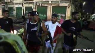 Libyan rebels patrol a street in Tripoli