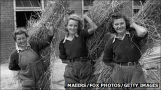 Land Girls carrying straw in 1941 (Photo: Maeers/Fox Photos/Getty Images)
