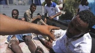 Two men accused of being mercenaries fighting for Muammar Gaddafi sit in a rebel vehicle in Tripoli