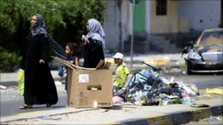 A family walks past a pile of garbage in the Abu Salim district of Tripoli