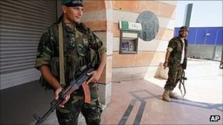 Libyan rebels stand guard outside a bank in Tripoli