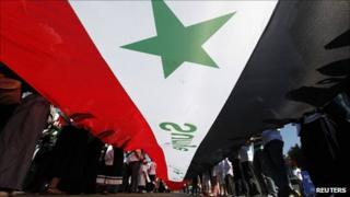 Syrian opposition demonstrators living in Turkey wave a huge Syrian national flag during a protest against President Bashar al-Assad in central Istanbul on 28 August 2011