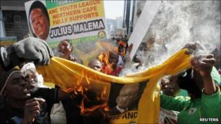 ANC supporters burning a Jacob Zuma T-shirt