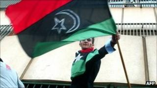 A man waving the rebel Libyan flag at the Harare embassy (24 August 2011)