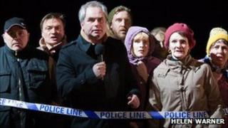 A crowd of people near police tape - London Road production photo by Helen Warner