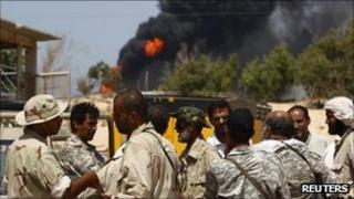 Rebels talk at the control station of an oil refinery outside the town of Brega, August 28, 2011