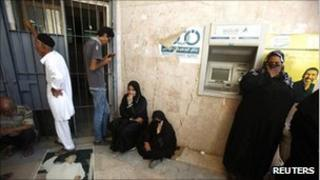 People waiting outside a Tripoli bank