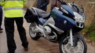 Policeman stood next to motorbike