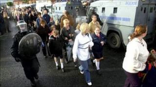 children walk to school past police lines during holy cross dispute