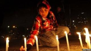 A child lights a candle outside TVN national television in Santiago, Chile, 2 September 2011