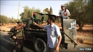 An anti-Gaddafi fighter receives a flag with the colours of the interim government in Tarhouna, 70 km (40 miles) north of Bani Walid, 3 September 2011