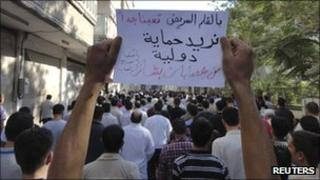 "People protest against President Bashar al-Assad in the city of Suqba, 30 August 2011. The banner reads: ""Need international intervention to protect us from Bashar's gangs"""