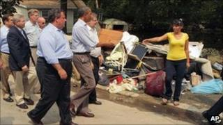 New Jersey Gov. Chris Christie looks on as President Barack Obama greets a woman as he visits areas damaged by Hurricane Irene, 4 Sept. 2011, in Wayne, NJ
