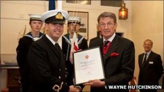 Sub Lieutenant Benjamin Nash (l) gets the award from Mr John Thurston of the Honourable Company of Gloucestershire