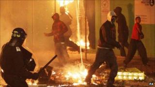 Rioters and policeman during London riots