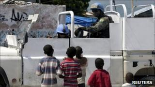 Brazilian peacekeepers in a a vehicle talk to Haitian children in Port-au-Prince