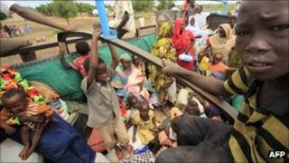 Displaced people ride a lorry to return to their homes in Sudan's Blue Nile region, 6 September 2011