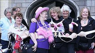 Women stand in front of chain of bras