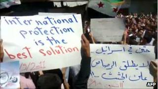 "An image grab from footage uploaded on YouTube on 9 September 2011 shows a protester holding up a sign (L) calling for international UN intervention in Syria during a protest in Kisweh, on the outskirts of Damascus; Arabic writing on the placard on the right reads: ""Even in Israel, they don't shoot at corpses"""